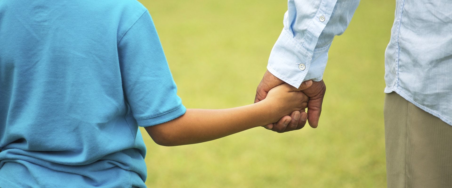 Image of child and adult holding hands.