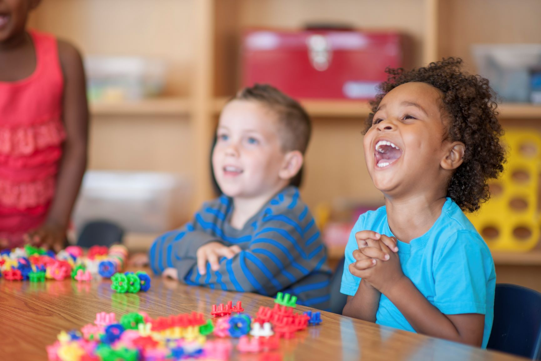 Preschool children are playing with toy blocks and laughing together at a classroom table.