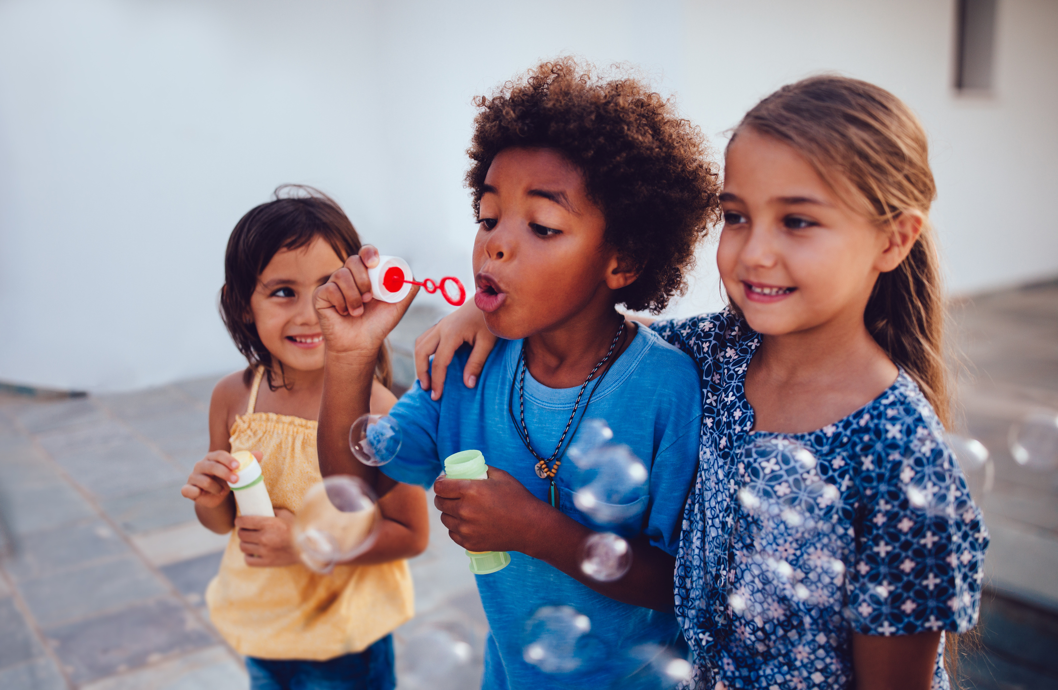Group of happy children outside playing and blowing bubbles.